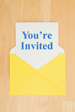 Youre Invited message on white card with a yellow envelope on a desk