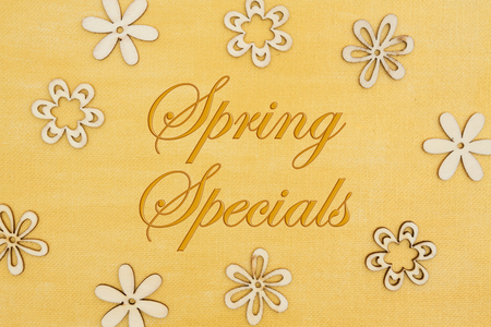 Spring Specials message with wood flower petals on hand painted distressed gold canvas