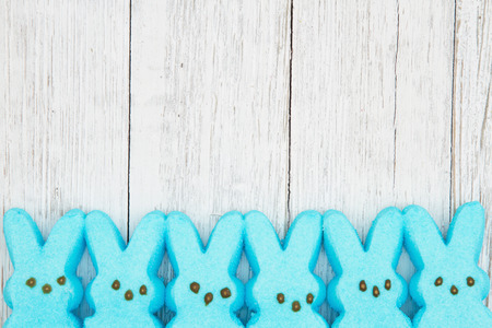 Blue candy bunnies on weathered whitewash textured wood background with copy space for your Easter message