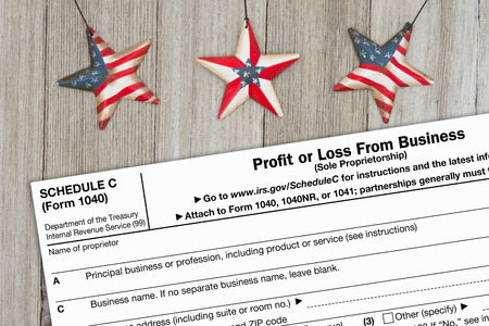 A US Federal tax 1040 schedule C income tax form on weathered wood with USA stars
