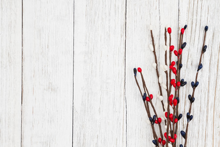 Red, white and blue berry spray on weathered whitewash textured wood background with copy space for your message