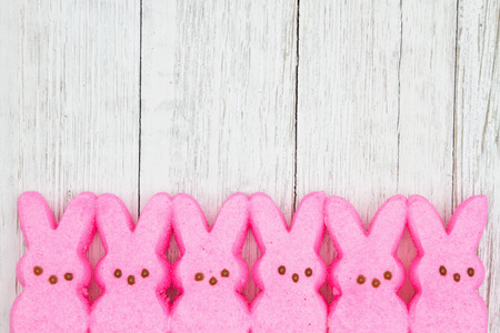 Pink candy bunnies on weathered whitewash textured wood background with copy space for your Easter message