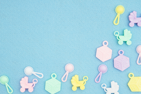 Baby strollers, abc blocks and rattles on an blue textured material with copy space for your baby message