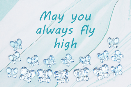 May you always fly high message with blue glass butterflies on  blue textured watercolor paper Stock Photo