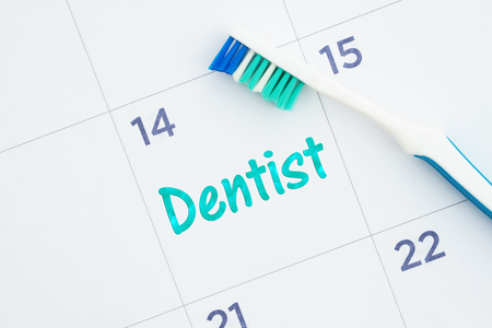 Schedule a dentist appointment message on a monthly calendar with a toothbrush Reklamní fotografie