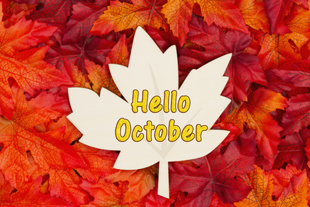 Hello October message, Some fall leaves and a wood maple leaf with text Hello October