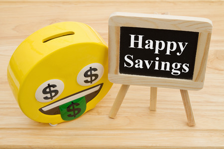 Learning how to save money, A coin bank on a desk with chalkboard with text Happy Savings