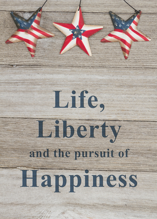USA patriotic message, USA patriotic old flag on a stars with weathered wood with text Life, Liberty and the pursuit of Happiness Stock Photo