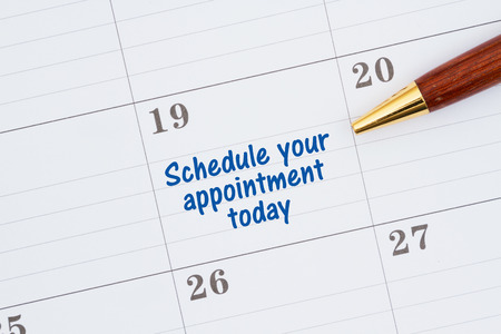 Scheduling your appointment today on a monthly calendar with a pen Foto de archivo