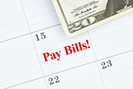 Time to pay the bills  message with a monthly calendar with 20 dollar bills