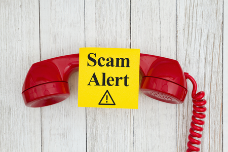 Scam alert message on sticky note on retro red phone handset on weathered whitewash textured wood Archivio Fotografico