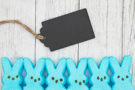 Blue candy bunnies with gift tag on weathered whitewash textured wood with copy space for your Easter message