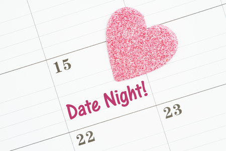 Scheduling your date night message with a monthly calendar with a pink heart