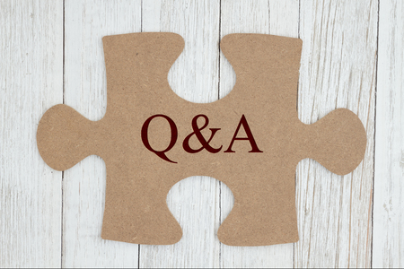 Getting your questions answered, Q&A text on a cardboard puzzle piece on weathered whitewash textured wood Stock Photo