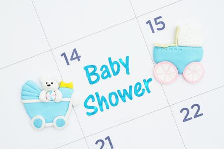Babyparty-Einladung auf einem Monatskalender mit blauen Kinderwagen Standard-Bild