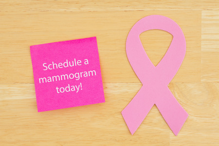 Reminder to schedule mammogram pink cancer ribbon on a sticky note on textured desk wood