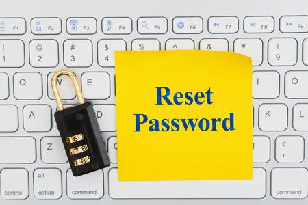 Passwort mit Zahlenschloss auf einer Tastatur mit Haftnotiz zurücksetzen Standard-Bild