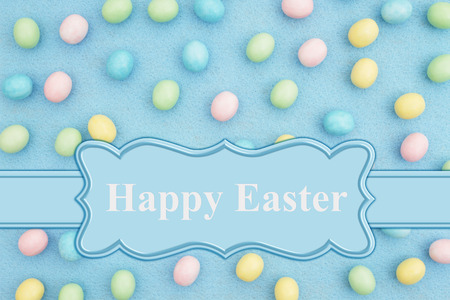 Happy Easter card with candy Easter egg on pale blue material 写真素材