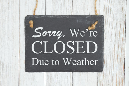 Closed due to weather sign, Sorry were Closed text on a hanging retro chalkboard on weathered whitewash textured wood
