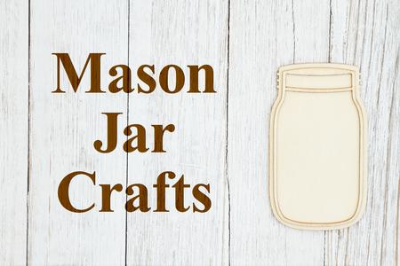 Mason jar crafts text with a wood mason jar on weathered whitewash textured wood Stockfoto