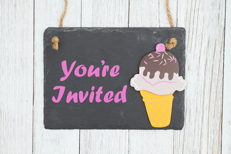 Youre invited text with an ice cream cone on weathered whitewash textured wood background