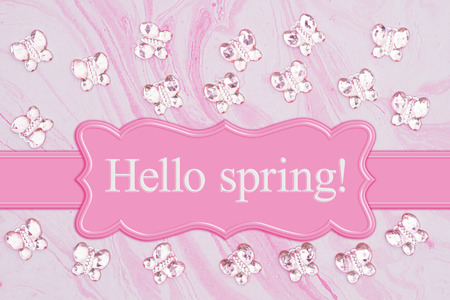 Hello Spring message with pink glass butterflies on  pink textured watercolor paper Stock Photo