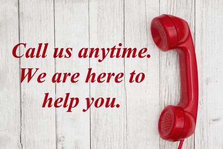 Call us anytime we are here to help text with retro red phone handset on weathered whitewash textured wood