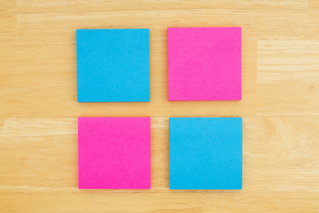 Four blank sticky notes on textured desk wood background you can use as a mockup Standard-Bild