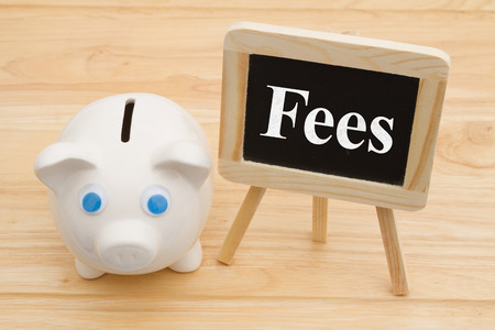Knowing your bank fees, A piggy bank on a desk with chalkboard with text Fees Stock Photo