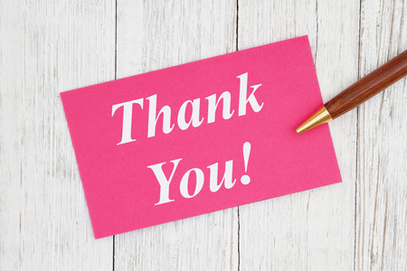 Dziękuję tekst na różowej karcie z długopisem na wyblakłym, bielonym teksturowanym drewnie Zdjęcie Seryjne