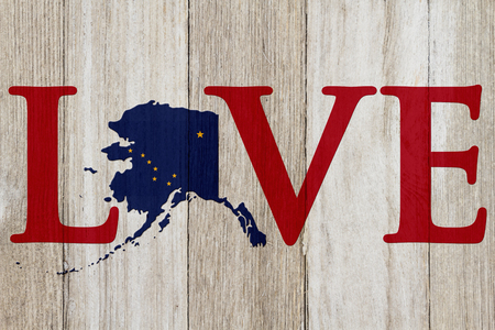 Love Alaska message with the Alaska state map in the Alaska flag colors on weathered wood