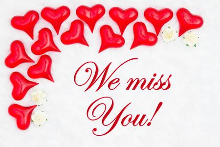 Wir vermissen deine Nachricht mit roten Herzen auf weißem Stoff und Rosenknospen