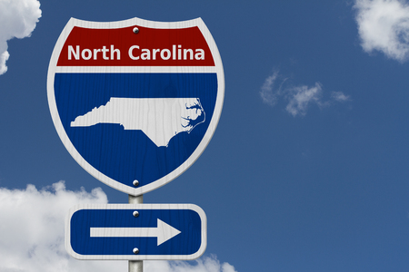 Road trip to North Carolina, Red, white and blue interstate highway road sign with word North Carolina and map of North Carolina with sky