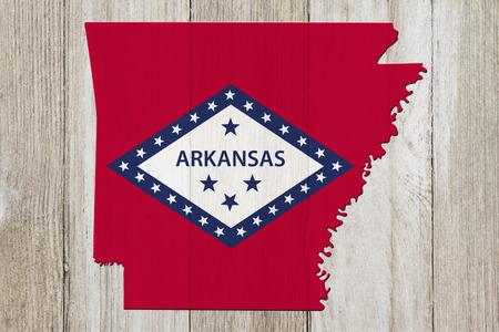Map of Arkansas in the Arkansas flag colors on weathered wood Reklamní fotografie