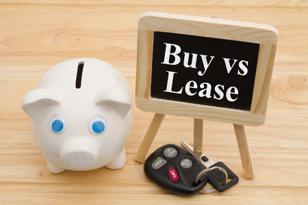 Learning whether to buy or lease car, A piggy bank on a desk with chalkboard and car keys with text Buy or Lease