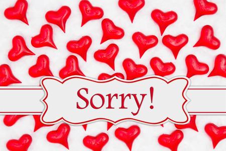 Sorry message with red hearts on white plush textured fabric