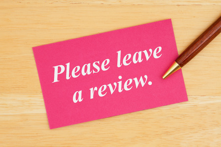 Please leave a review text on pink card with pen on wood desk
