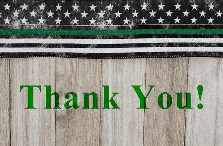 Thank You message on an American thin green line flag for border patrol agents over weathered wood