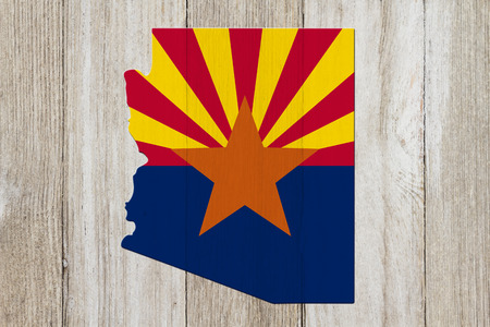 Map of Arizona in the Arizona flag colors on weathered wood