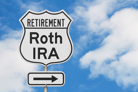 Retirement with Roth IRA plan route on a USA highway road sign with sky background Stok Fotoğraf