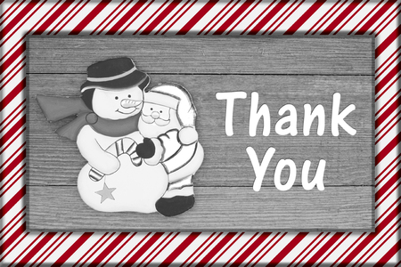 Old fashion Christmas message, A retro snowman hugging Santa Claus on weathered wood  and candy cane border with text Thank You
