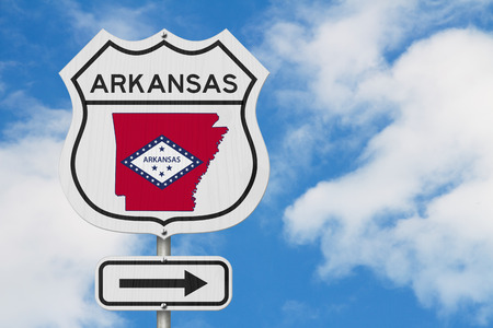 Arkansas map and state flag on a USA highway road sign with sky