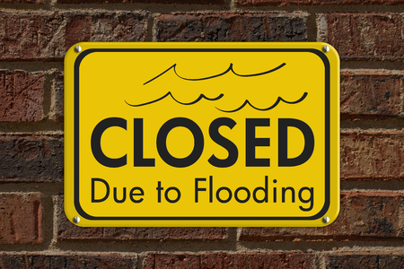 Closed Due to Flooding yellow sign on brick wall building