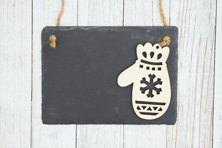 Blank hanging chalkboard with a mitten on weathered whitewash textured wood background you can use as a mockup