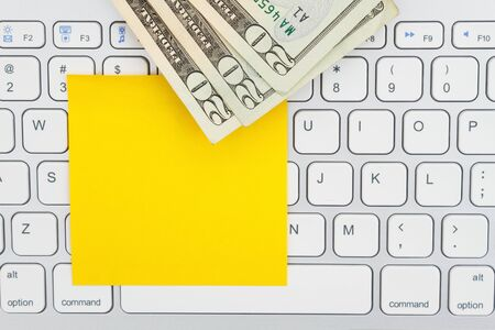 Money on a computer keyboard with sticky note for your making money message