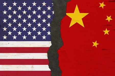 American and Chinese flags that are torn apart with dark separation material 写真素材