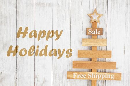 Happy Holiday text with wood Christmas tree on weathered whitewash textured wood