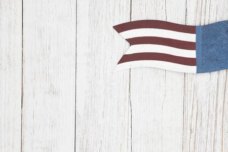 Red, white and blue retro American flag on weathered whitewash textured wood background with copy space for your message