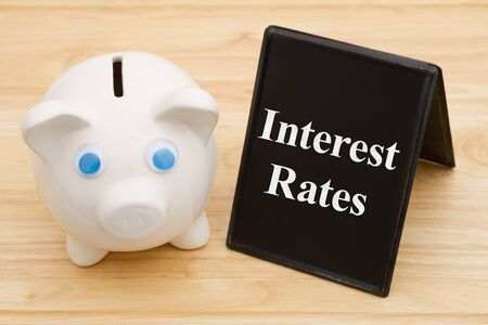 Knowing your banks interest rates, A piggy bank on a desk with chalkboard with text Interest Rates