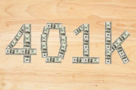 Retirement 401k text made from 100 dollar bills on a wood desk 写真素材